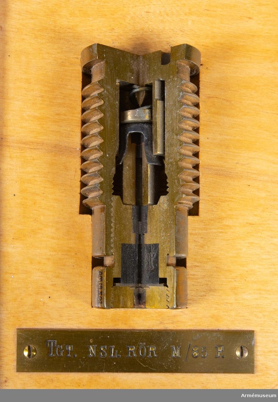 4 st tändrör av olika modeller, fastmonterade i trälåda av ek. Består av 5 delar: 1 st förvaringslåda av trä, mått: 270x270x78 mm, färg brun. 1 st lätt nedslagsrör m/1885, försök. Genomskuret, av mässing, längd 57 mm, största diameter: 28 mm (genomskuret). 1 st tungt nedslagsrör m/1985, försök. Genomskuret, av mässing, mått: längd: 65 mm största diameter: 31 mm. 1 st nedslagsrör m/1912 med detonator av mässing, koppar och järn (genomskuret). Mått: längd med detonator 222 mm,  största  diameter: 50 mm. 1 st dubbelrör m/1917 med detonator av mässing, koppar och järn. (genomskuret). Mått: längd med detonator: 180 mm, största  diameter: 60 mm.  Röret har temperingsskala från 4 till 60.