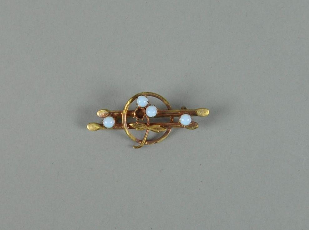 Brosje av gullfarget metall med månestensperler, hvorpå en perle mangler.