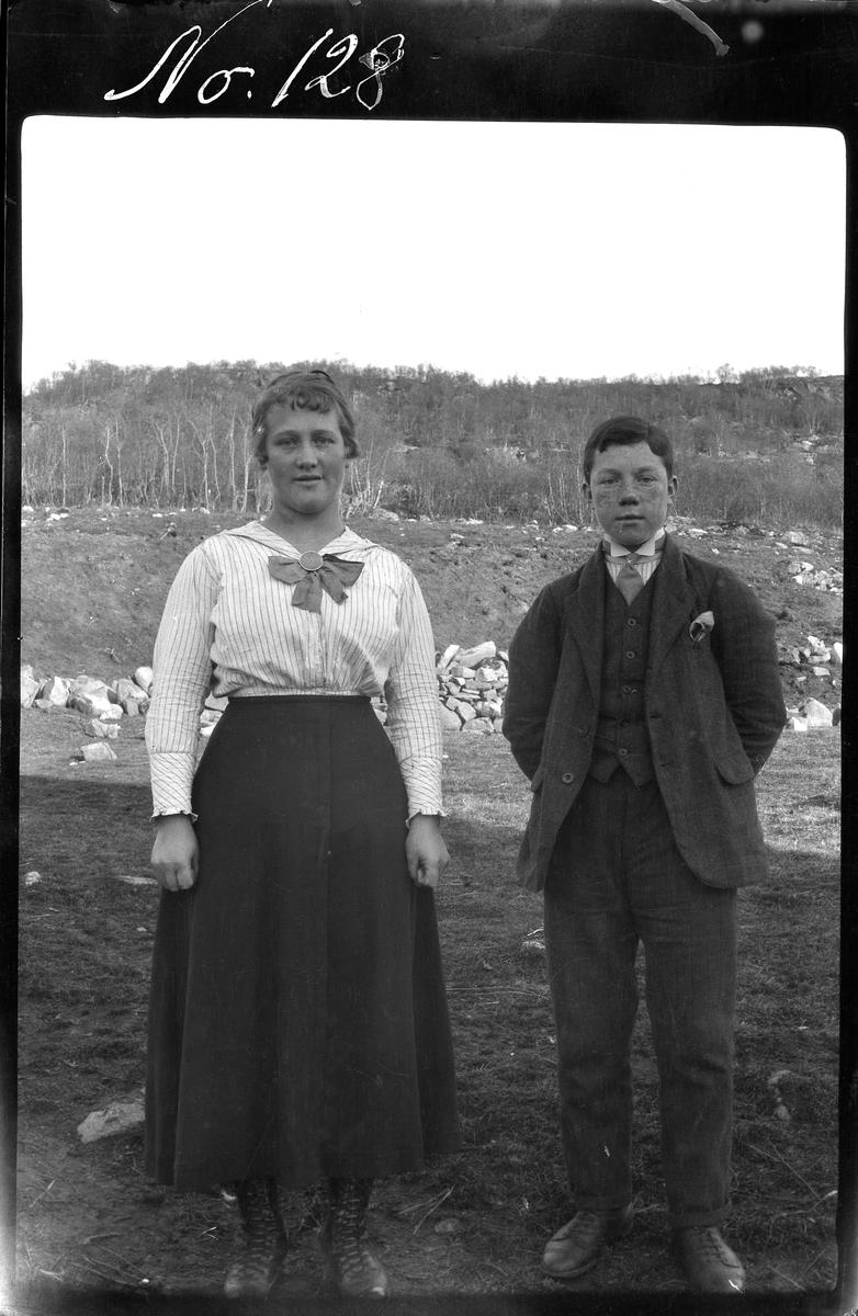 Portrett av kvinne og en unggutt stående utendørs.