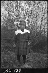 Portrett av liten pike, fotografert utendørs.