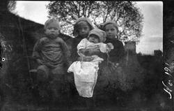 Portrett av fire små barn, fotografert sittende utendørs.