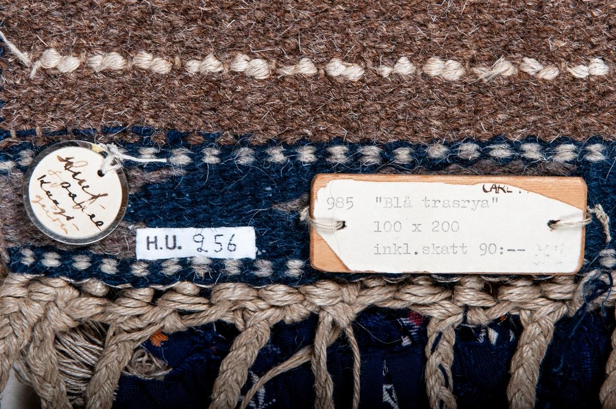 """Trasrya, flossaväv, 210 x 100, """"Blå varpryan"""". Varp av grovt oblekt lingarn; vävt av hårgarn. Kortsidornas smalbårder i röllakan i blått och grått. Nocken ylle och bomullstrasor i olika blå färger, något rött och mönstrat samt vitt lingarn. Flätad frans. Sign M.M.F. Inköpt på MMF utställning på Liljevalchs 1934. Äldre katalogisering av Elisabeth Thorman (enl. uppgift).  Längd: 210 cm          Bredd: 100 cm exkl. frans Fransens längd: ca 15 cm Varp: 3 tr/cm            Inslag: ca 6/cm Varp 4 tr grågult, oblekt troligen lingarn, botteninslag ljusbrunt, blått, vitt och melerat grått/blågrönt/ljusrött djurhårsgarn. 12 botteninslag mellan nockraderna. 1 tr och 2 tr grågult oblekt lingarn och trasor av olika material i flera nyanser blått i nocken, rya nockens längd: ca 2 cm. 4 knutar/dm på längden 8 knutar/dm på bredden. Mittpartiet melerat i flera nyanser blått små fyrkanter i oblekt jämnt fördelade över mittpartiet, runt omkring en fyrkantig bård av oblekt, vid kortsidorna en bård i rölakan av viggformer, därom en twistrand. Närmare beskrivning se katalogkort. Vävnaden avslutas med knuten frans av varpen.  Vid ena hörnet invävd signatur MMF i blått djurhårsgarn.  Kanal fastsydd längs ena kortsidan.  Komponerad av Märta Måås-Fjetterström 1934  Se Lundgren: Märta Måås-Fjetterström och vävverkstaden i Båstad 1968, sid 114.  Ulla-Britta Sandström april 1980  Foto Nordiska museet: 393. O.c. (se katalogkort)."""