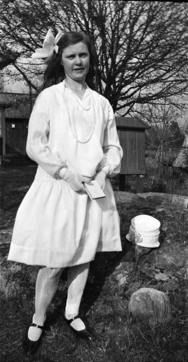 47137e9cb7e0 Flicka som står utomhus i konfirmationskläder, långt pärlhalsband och stor  rosett i håret. Både