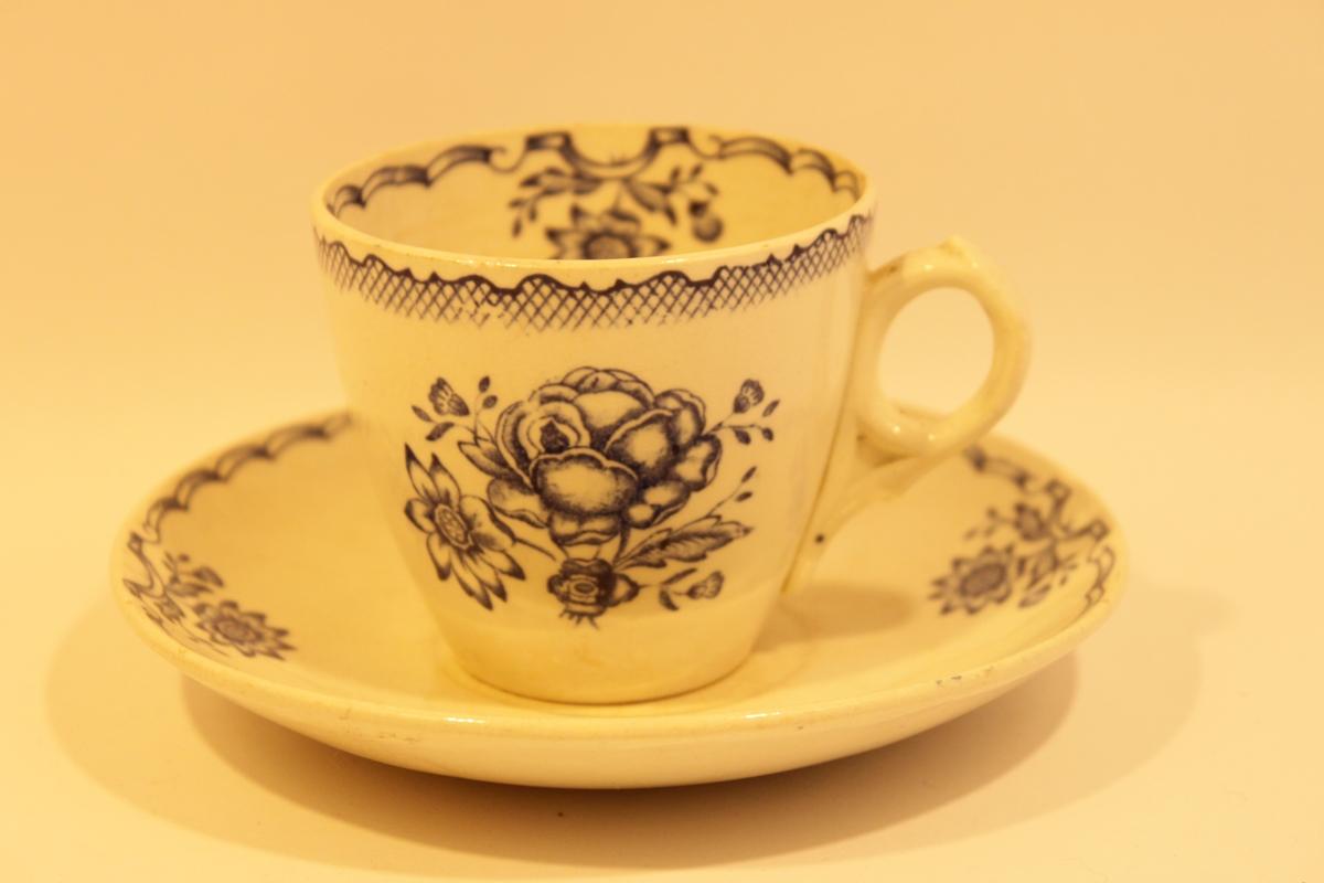 Vit kaffekopp och fat med blå dekor. Blommönster och girlander på både in- och utsidan av koppen samt på fatets ovansida. Kaffekoppen heter Bukett och tillverkades av Gustafsberg mellan åren 1936 och 1939.
