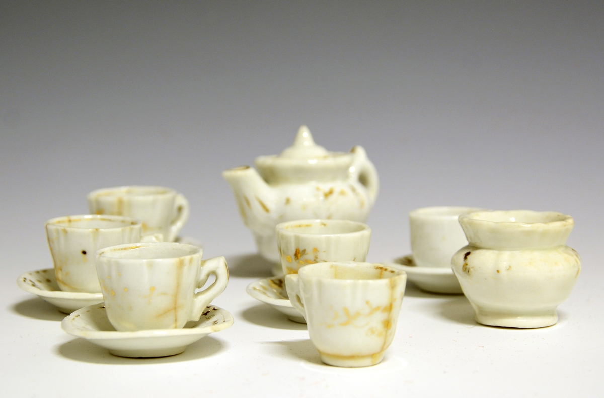 Dukkeservise bestående av tekanne, sukkerkopp, fem kopper og fire skåler. Hvit glasur me dgullstaffasje. Relieff i godset.