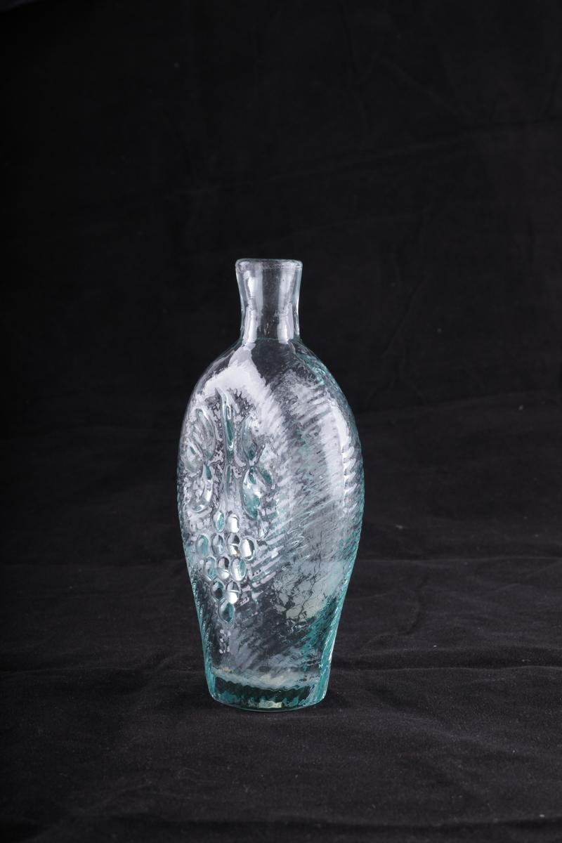 Flaske i grønnlig glass, blåst i form. Rommer en halv pegel. Motivet på den ene siden viser den norske løve, på den annen en drueklase.