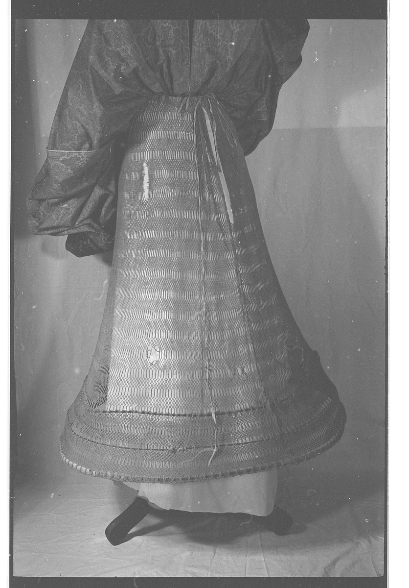 Krinoline.  Gård:Stai, Storelvdalen.  Gruppe:N1B.  Tråd, tekstil (hekling) Festet til 3 stål sirkler.  Hl. 89 cm. Omkrets 2, 5 m.  Trekk band i livet.  Kjøpt ved auksjon på Lillehammeren, Stai
