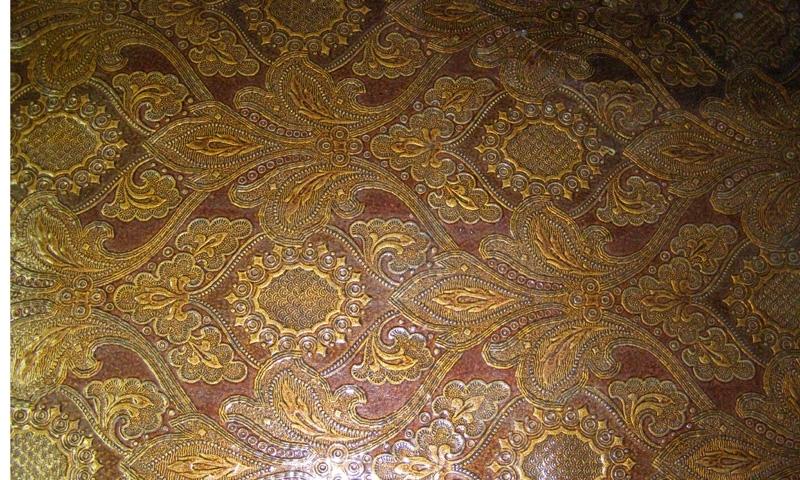Brun papperstapet med guldfärgade stiliserade blommor.