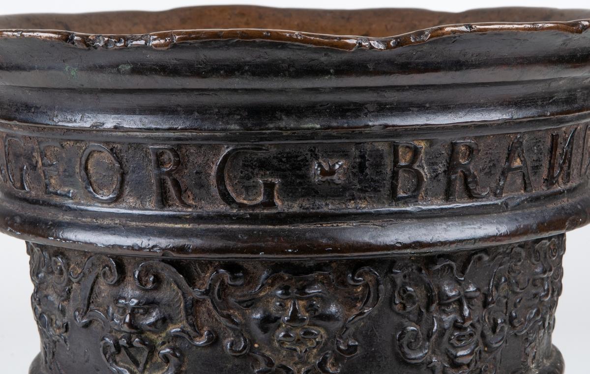 Mortel av brons, från 1683. Kanten upptill är vidgad utåt, något skadad och blandsliten. Inga handtag finns och ingen stöt.  Runt om är är den prydd med två reliefband med ansikten, text i relief: Georg Brandt Anno MDCLXXXIII.   höjd 24 cm, diameter 25 cm.
