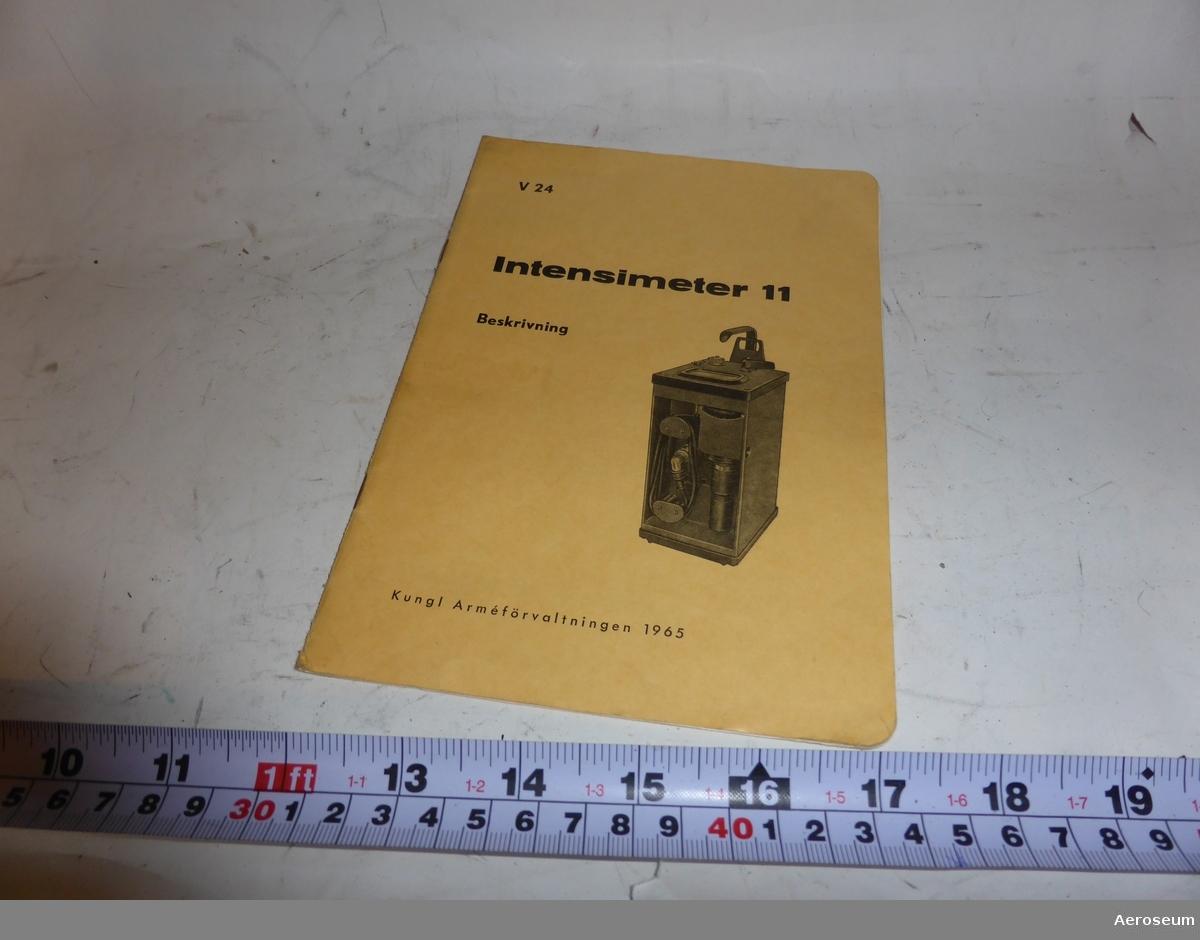 Intensimeter 11, nr 2303 och nr 2133. Placerade i varsin lackad trälåda. I båda lådorna finns, utöver en intensimeter, en bärsele, batteribox med sladd, beskrivningshäfte, plastpåsar, och klämmor. På en av lådorna hänger det även en liten nyckel som kan låsa lådorna så att locket inte kan öppnas. Tillverkade av Mullard.