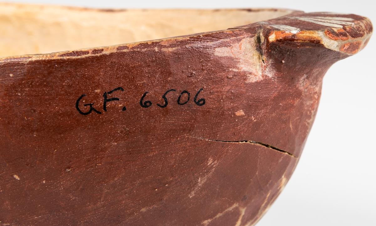 Ölgås av björkträ, i form av en liggande fågel, utan huvud. Rödmålad med blå hals och vita ränder på den korta stjärten. Längd 30cm, bredd 13cm. PÅ den flata sidan är ristat MPD och på sidan MPD 1856 i vit målning.