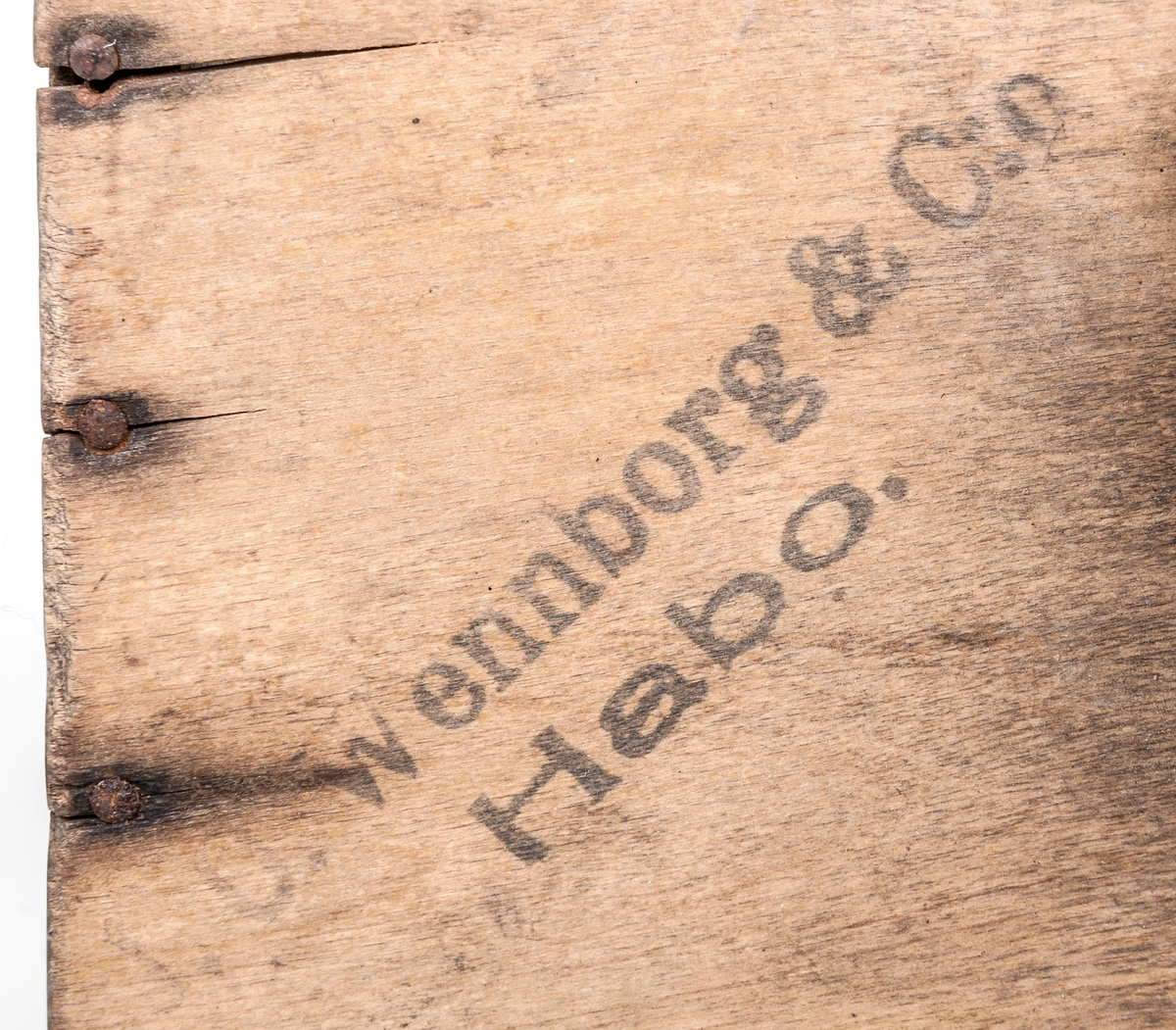 """Bärplockare. Trälåda med botten av svängda järntenar (kam). En kortsida öppen och motstående sida av läder. Handtag på ovansidan. Text; """"Wennborg & C:o Habo. Patent""""."""