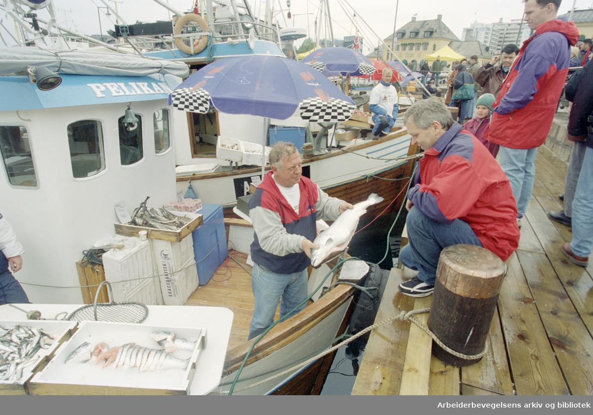 """Oslo: Havna. Diverse stemningsbilder. Fiskeskipper Jan Johannesen (t.v.) ombord på """"Pelikan"""" selger fisk til Harald Kristoffersen. 17. mai 1996"""