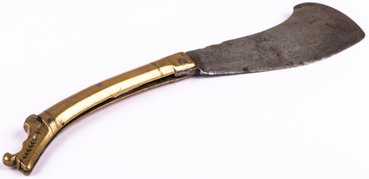 """Gästabudskniv med brett knivblad att fälla in i mässingskaftet. Gaffel, tvåhornig av järn. Hållare av mässing, skaft av mässing. Skaftet har dekoren av ett drakhuvud. """"R"""" stansat i bladet."""
