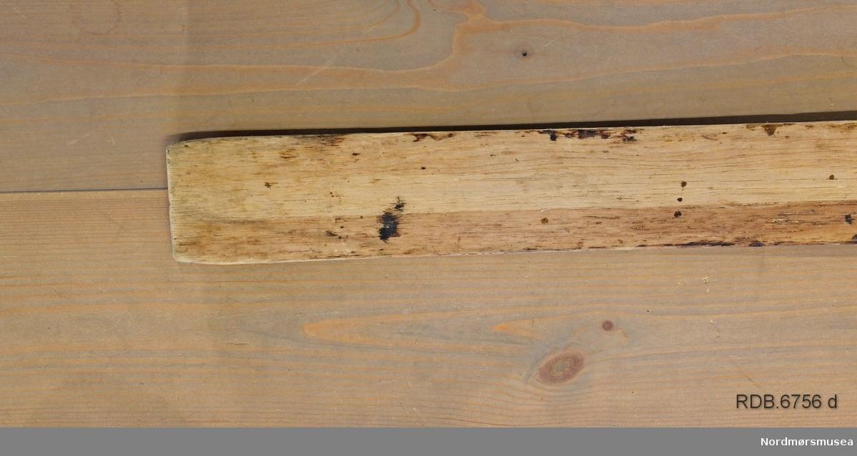 """Et heimeprodusert treski. Sålen på skiet er borte, slik at en kan se hvordan det er laget invendig. Overplata har mørke striper langs kanten og en lys stripe etter midten. Skiet er jevnbredt med tverr bakkant, bred brett med lav bøy. Skiet er bredest på midten og smalere bak- og framover. Spikermerker etter bindinger og fotplate som er fjernet. Innvendig er det 4 """"luftrom"""" som gjør skiet lettere."""