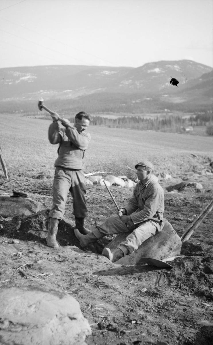 To mann med slegge og spett i gang med å dele en stor stein på jordet, antakelig på Linjordet i Østre Gausdal