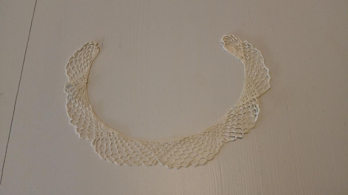 1 kjolekrave  Rund kjolehalskrave, heklet av hvitt bomullsgarn.  Gave fra fru Laura Finckelsen f. Hjortdahl, Oslo