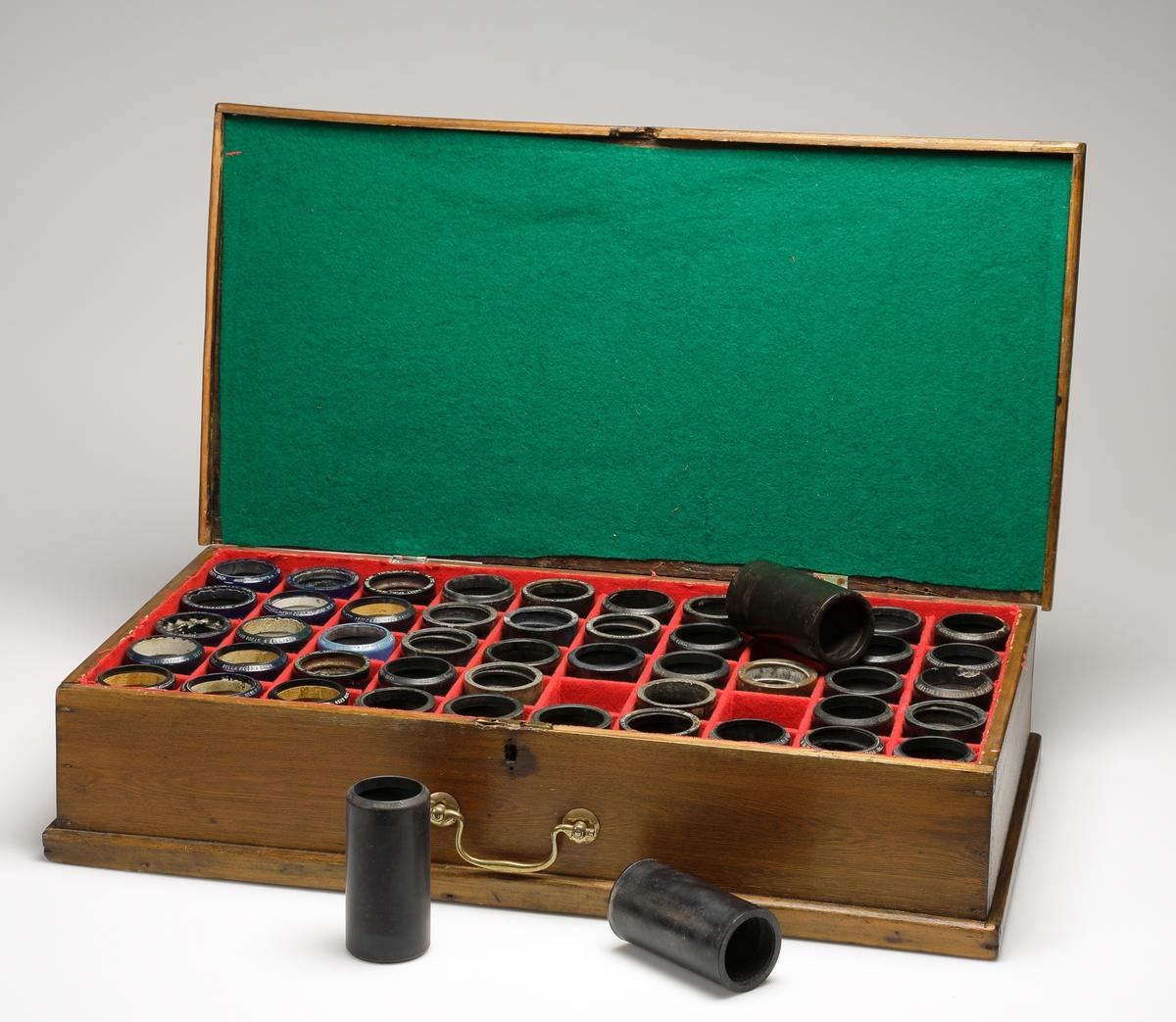 Schatull.  Rektangulär modell av brunbetsat trä. En bärring av mässing är fastsatt på långsidan. Inuti schatullet finns 50 st. fack, klädda med röd filt, avsedda för vaxrullar (samtliga finns). Locket är invändigt klätt med mörkgrön filt. Saknar märkning.