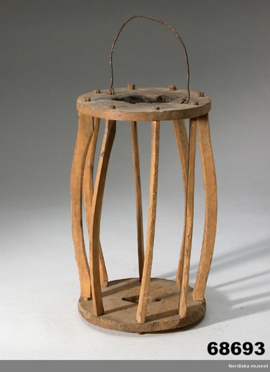Lykta av trä. Rund bottenplatta och rund takplatta och mellan dem 8 täljda intappade trästavar. Hål i botten- och takplatta. Smalt handtag av järntråd fäst i takplattan. Lyktan har ursprungligen varit klädd med troligen komage, våmb, men inga rester finns bevarade. 2019 har lyktan försetts med en ny fårnätmage och en ny ljushållare av trä och plåt.