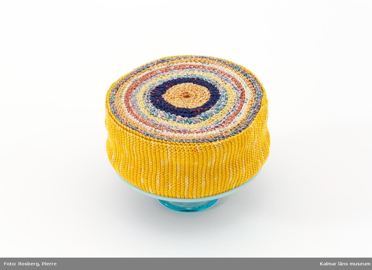 """Tårta i olika färger på blått tårtfat. Titel: """"Tårtfat""""."""
