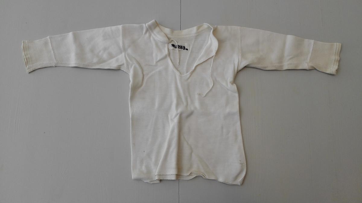 Form: Rett bol med sidesaumar.  2 undertrøyer for born.  Glatt isydd erme med brot. Rund halsringing med linning og splitt i front samanknytt med snorer.