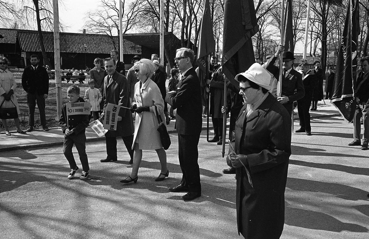 1:a majtåg. Demonstration. Längst till vänster går Bertil Karlsson (ordförande i stadsfullmäktige) och hans son, Berit Oscarsson (ungdomstalare för Sveriges Socialdemokratiska Ungdomsförbund), Åke Zetterberg (pastor och ordförande i Broderskapsrörelsen) samt Anna-Lisa Isaksson (ordförande i Fackens CentralOrganisation). Människor med fanor och vimplar. I bakgrunden syns Ahllöfsparken med scenen.  Olof Ahllöfs park, med scenen, skymtar i bakgrunden.