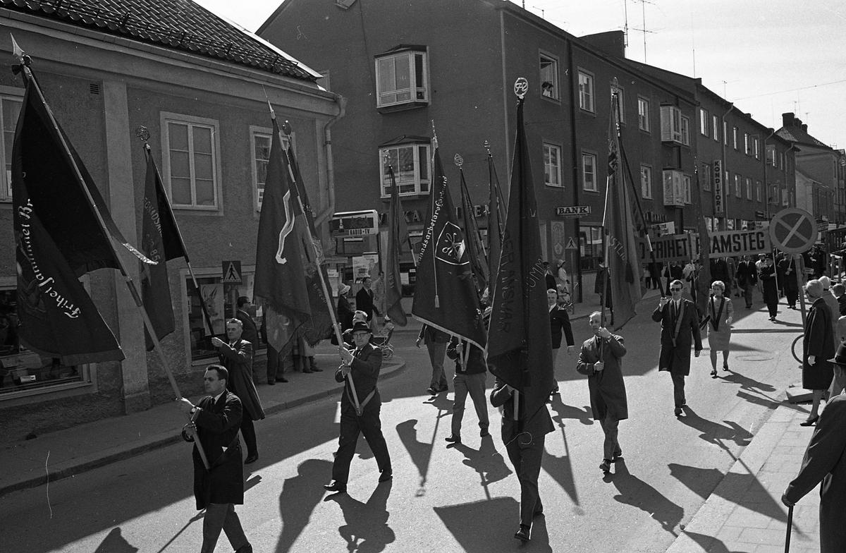 1:a majtåg. Demonstranter och fanbärare på Nygatan. Bland publik och barnvagnar skymtar AGA Radio - TV, Skandinaviska Banken och Konditoriet.