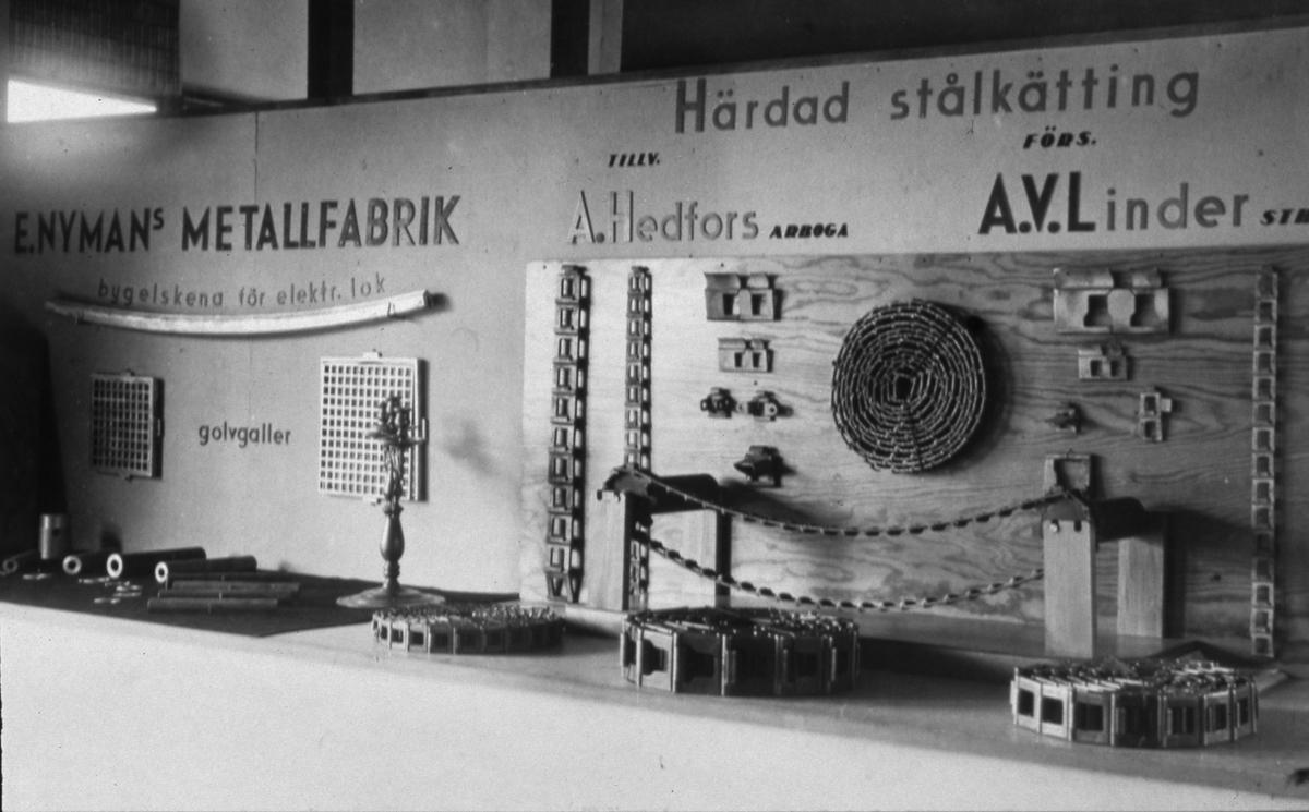 Nymans Metallfabriks monter bredvid Kättingfabrikens monter på Arbogautställningen. Kättingfabriken låg på Västerlånggatan. Kättingen tillverkades av A. Hedfors. Metallfabriken visar en bygelskena för elektriska lok och golvgaller. Där finns en ljusstake också. Kättingfabriken visar kättingar av olika grovlek och utseende.