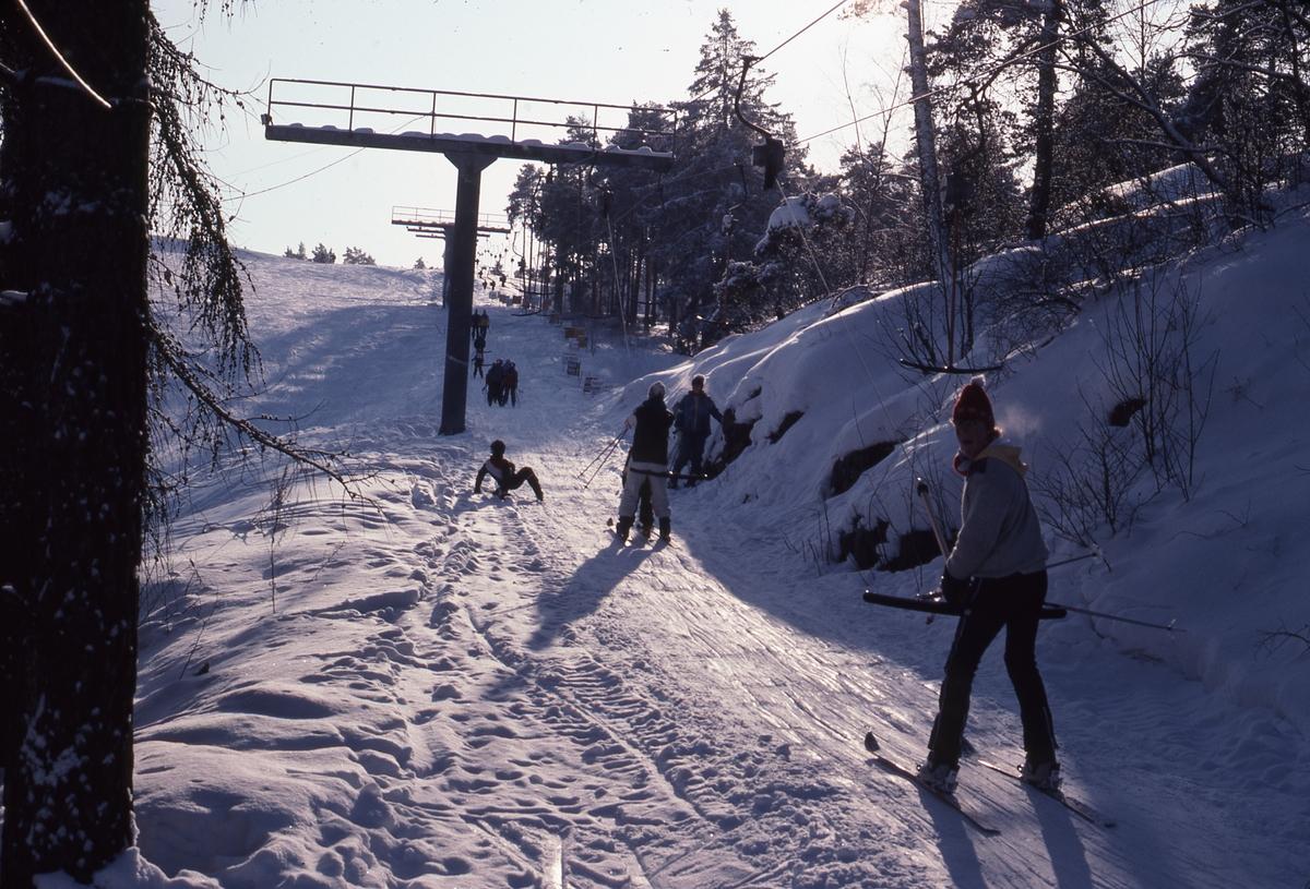 Slalomåkare i skidliften på väg uppför Teknikbacken.