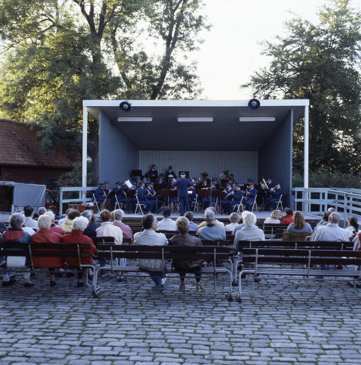 Arboga Blåsorkester uppträder på scenen i Olof Ahllöfs park. Publiken sitter på bänkar. Scenen är vitmålad och har en ramp på högra sidan.