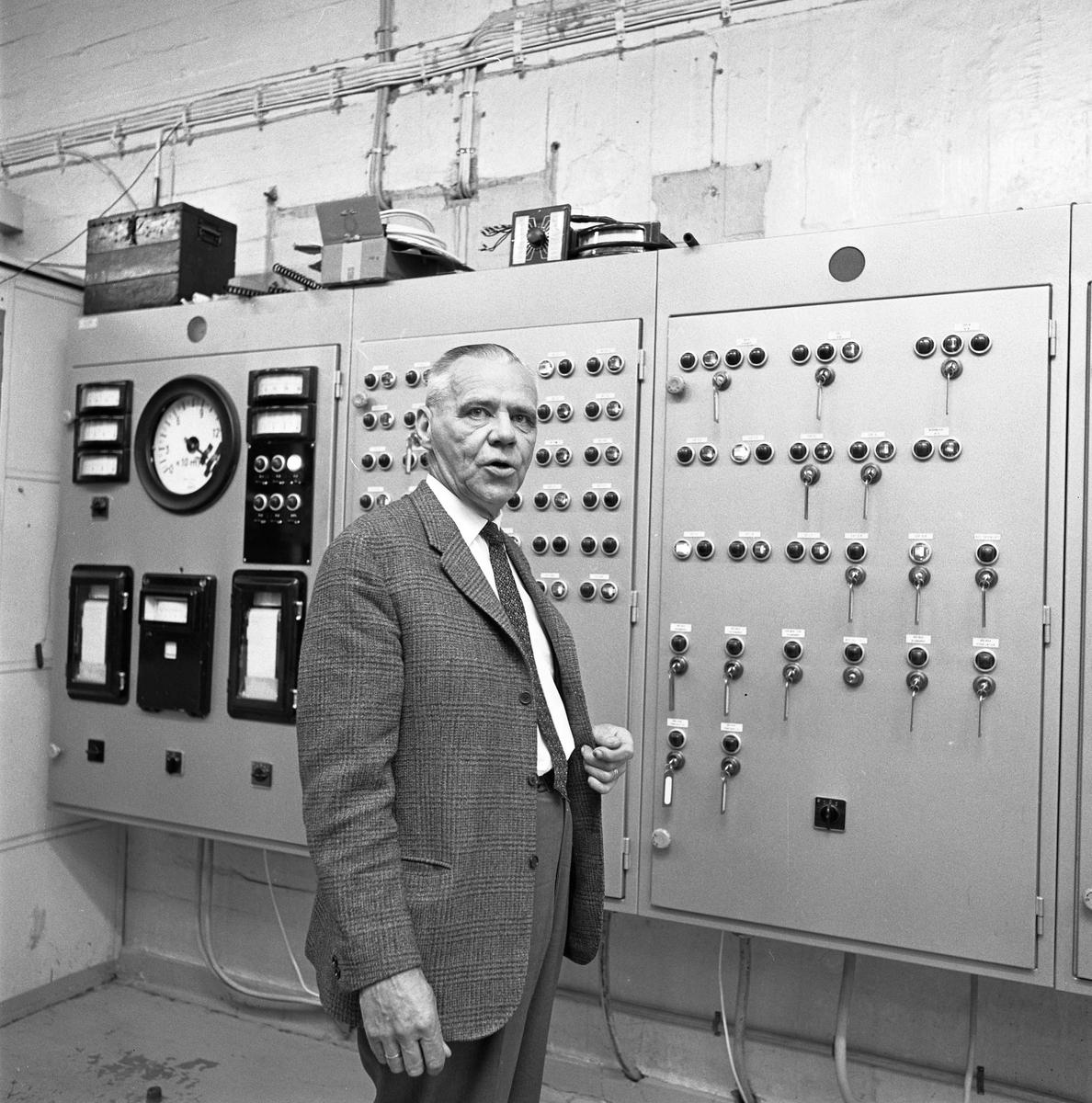 Alf Hedlund, maskinmästare vid Centrala Verkstaden Arboga, går i pension  Kostymklädd man i industrimiljö. Knappar och reglage.