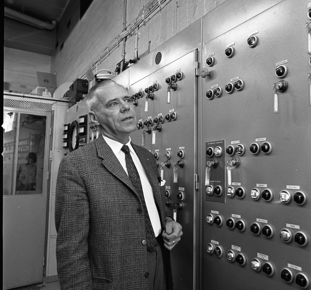 Alf Hedlund är maskinmästare på Centrala Verkstaden Arboga. Han är klädd i kostym och står vid en maskin med många knappar.