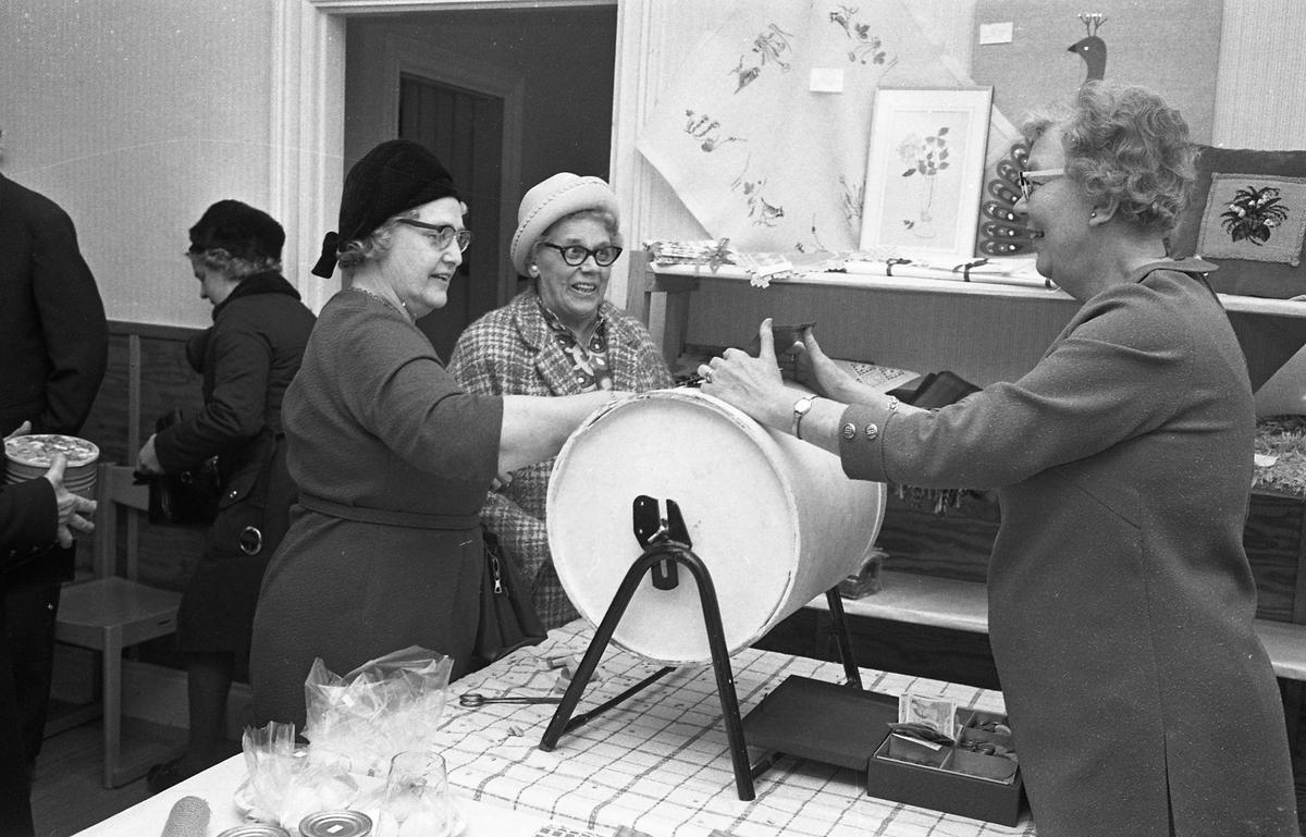 Arbetareföreningen ordnar försäljning. Kvinnor köper lotter. Handarbeten på hyllan.