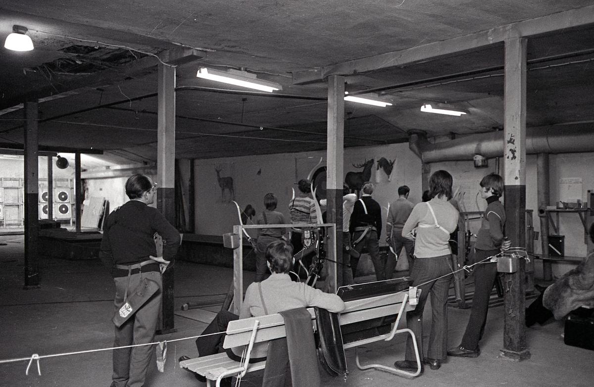 Inomhusträning hos Arboga Bågskytteklubb. Skyttar, står på rad, och skjuter med pil och båge mot måltavlor på väggen. Var och en har sitt koger hängande på höften. Två skyttar, samspråkar till vänster i bild. Tre personer sitter på en bänk, med ryggen mot fotografen, två av dem har ytterkläderna på sig. Lokalen ser ut att vara i en källare.