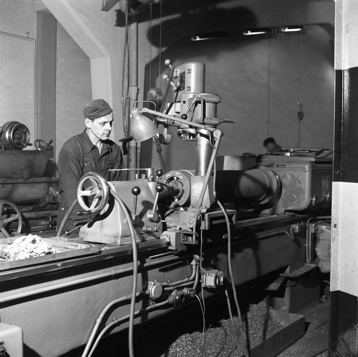 Arboga Maskiner, interiör En man arbetar vid en maskin, kanske en svarv, i en fabrikslokal. En annan man skymtar i bakgrunden. Företaget arbetar med borr- och slipmaskiner. Bilden är tagen i samband med att Arboga Maskiner firar 25-årsjubileum.  Läs om Arboga Maskiner i Reinhold Carlssons bok Arboga objektivt sett.