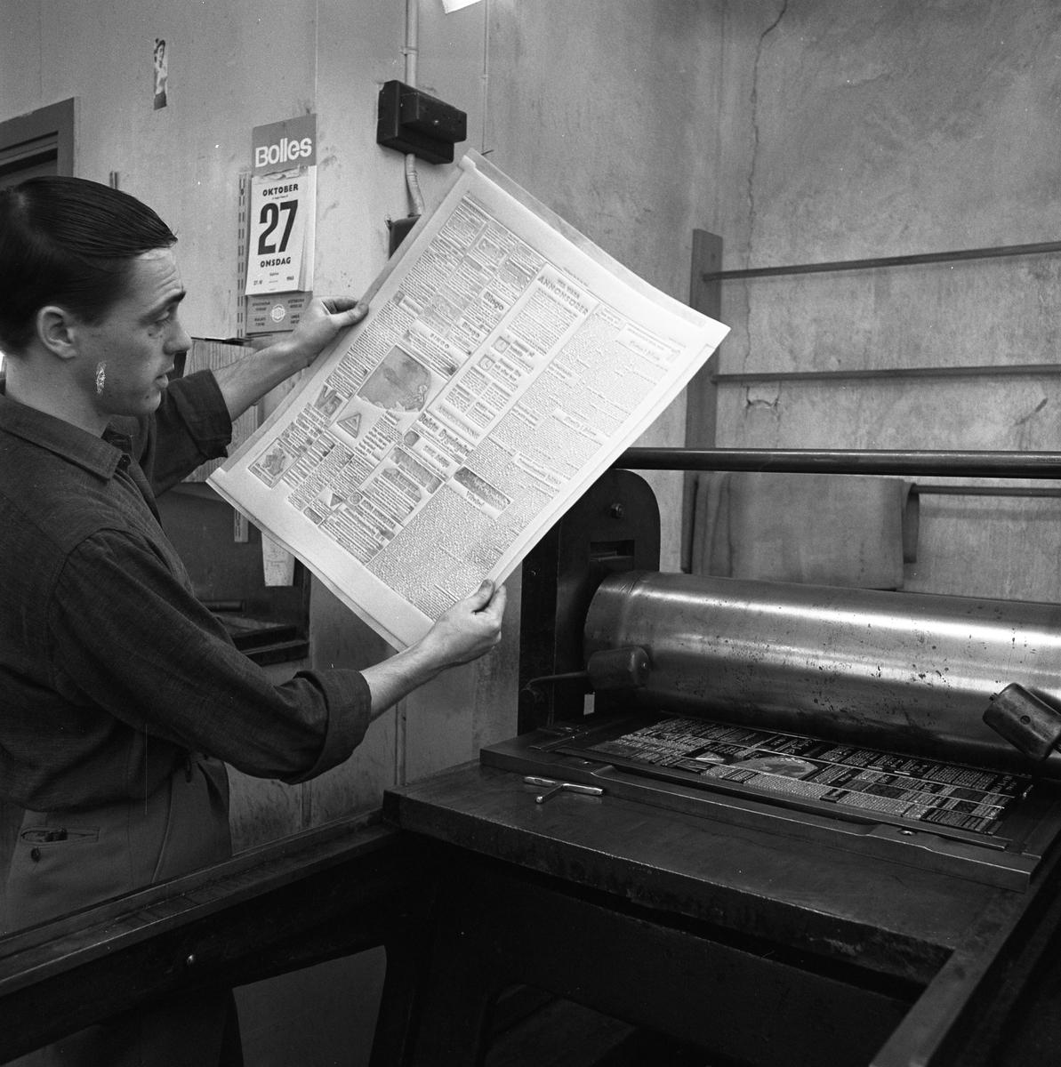 Arboga Tidning, personal och interiör. En man håller upp en tryckt plåt av en blivande tidningssida. I maskinen, framför honom, ligger den satta sidan.