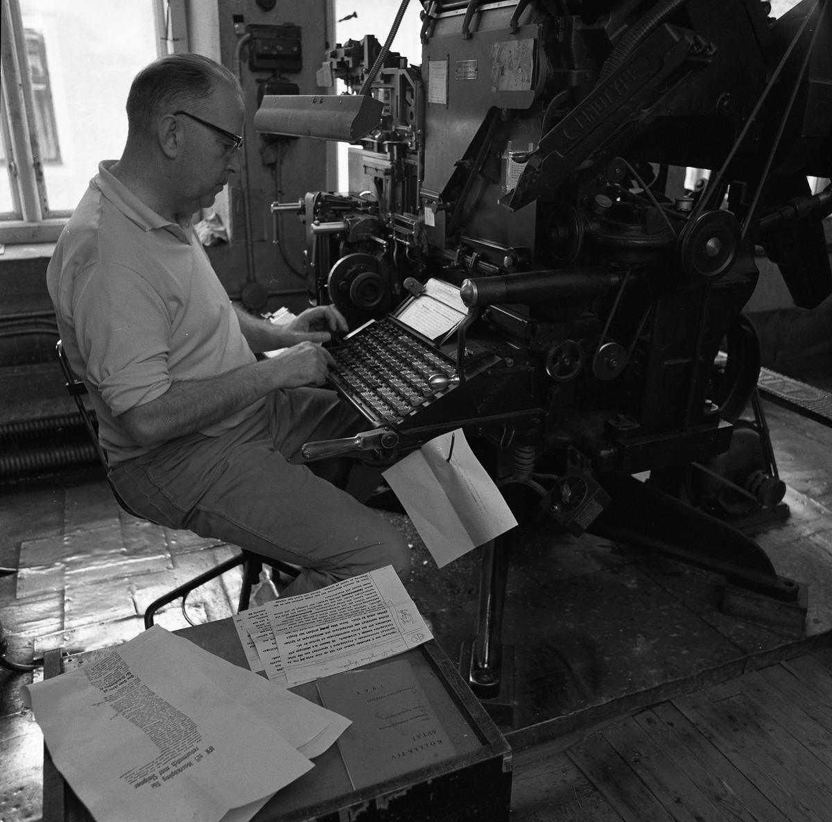 Arboga Tidning, personal och interiör. En man sitter vid en maskin. Maskinen har ett tangentbord som han skriver på. Vid sidan av mannen ligger papper utspridda.
