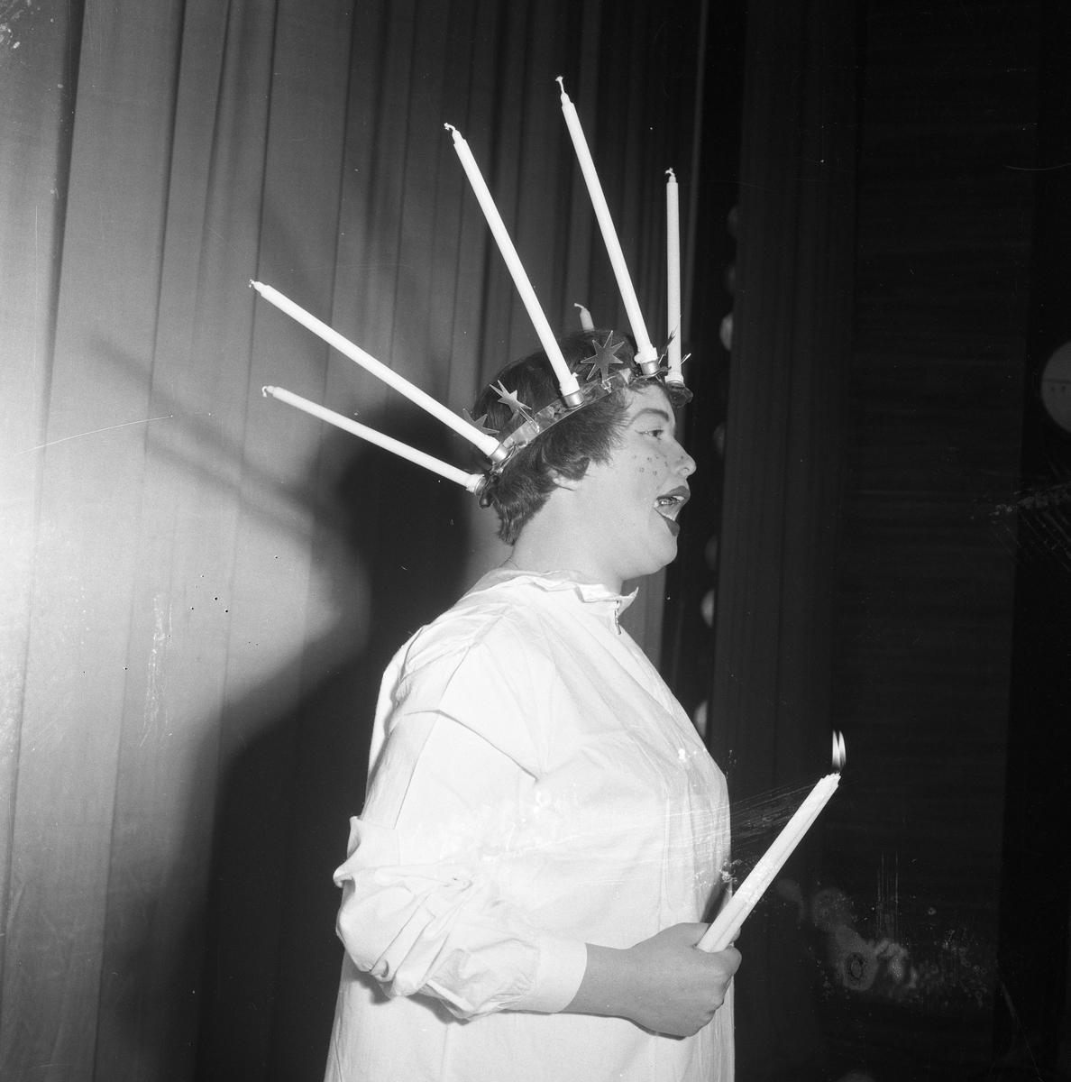 Arbogarevyn spelar upp sin Jubileumsrevy. Man utklädd till Lucia med långa stearinljus i kronan och ett ljus i handen.
