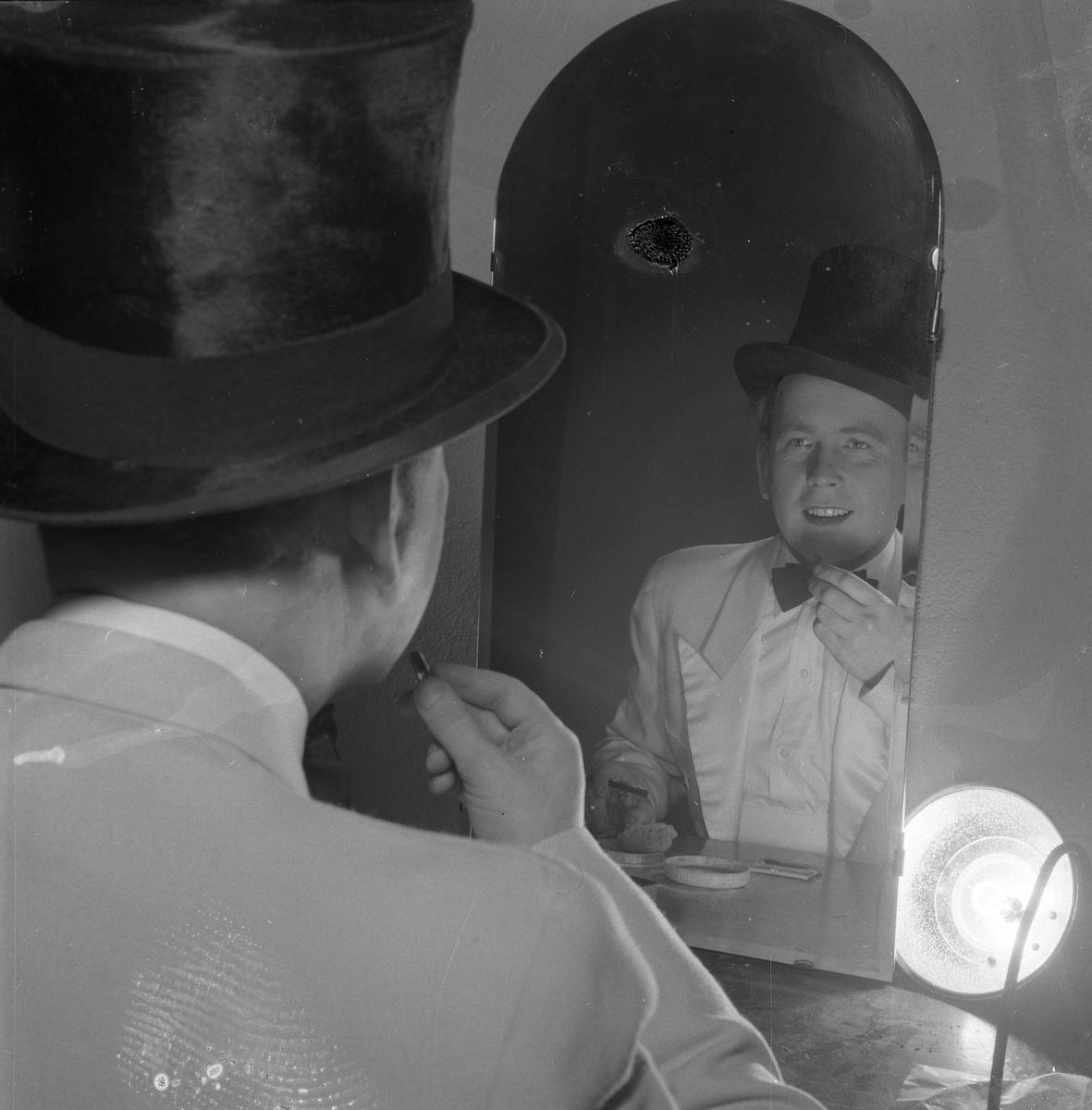 Arbogarevyns medlemmar spelar upp sin Jubileumsrevy. Rune Lindqvist sitter i logen och sminkar sig framför spegeln. Han är iklädd stormhatt och fluga.