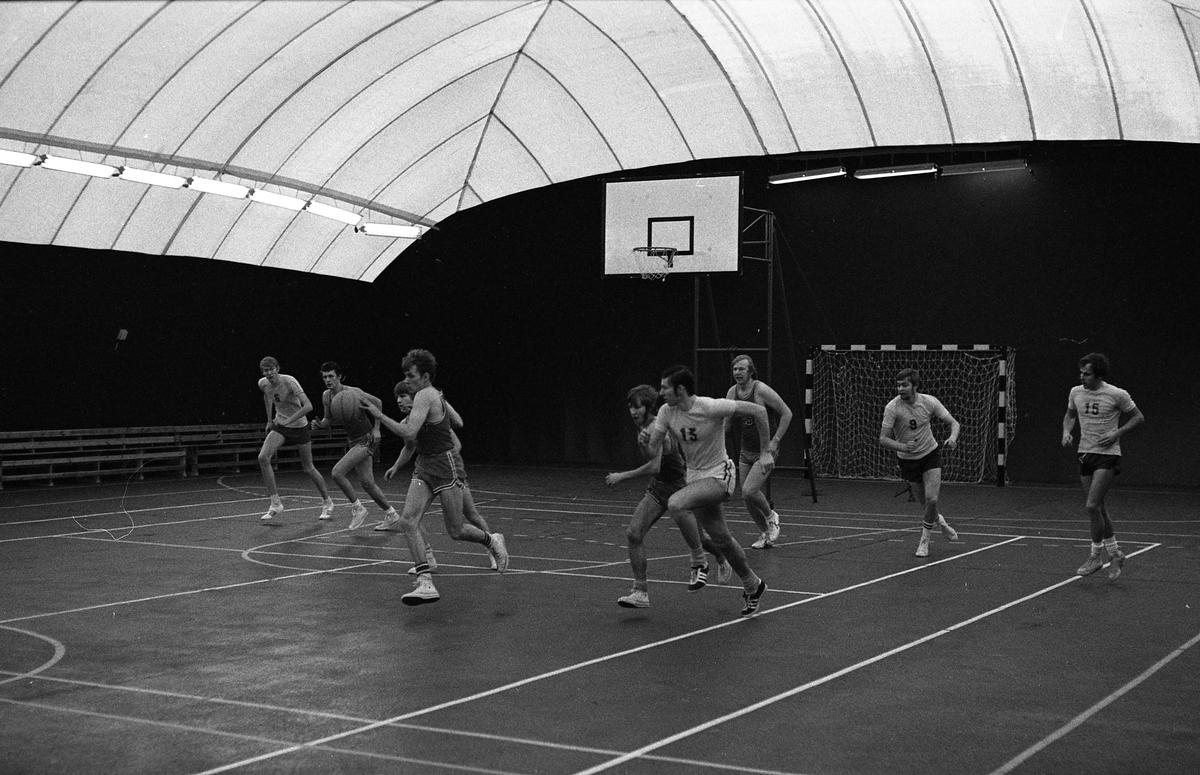 Herrlag spelar basket i plasthallen.