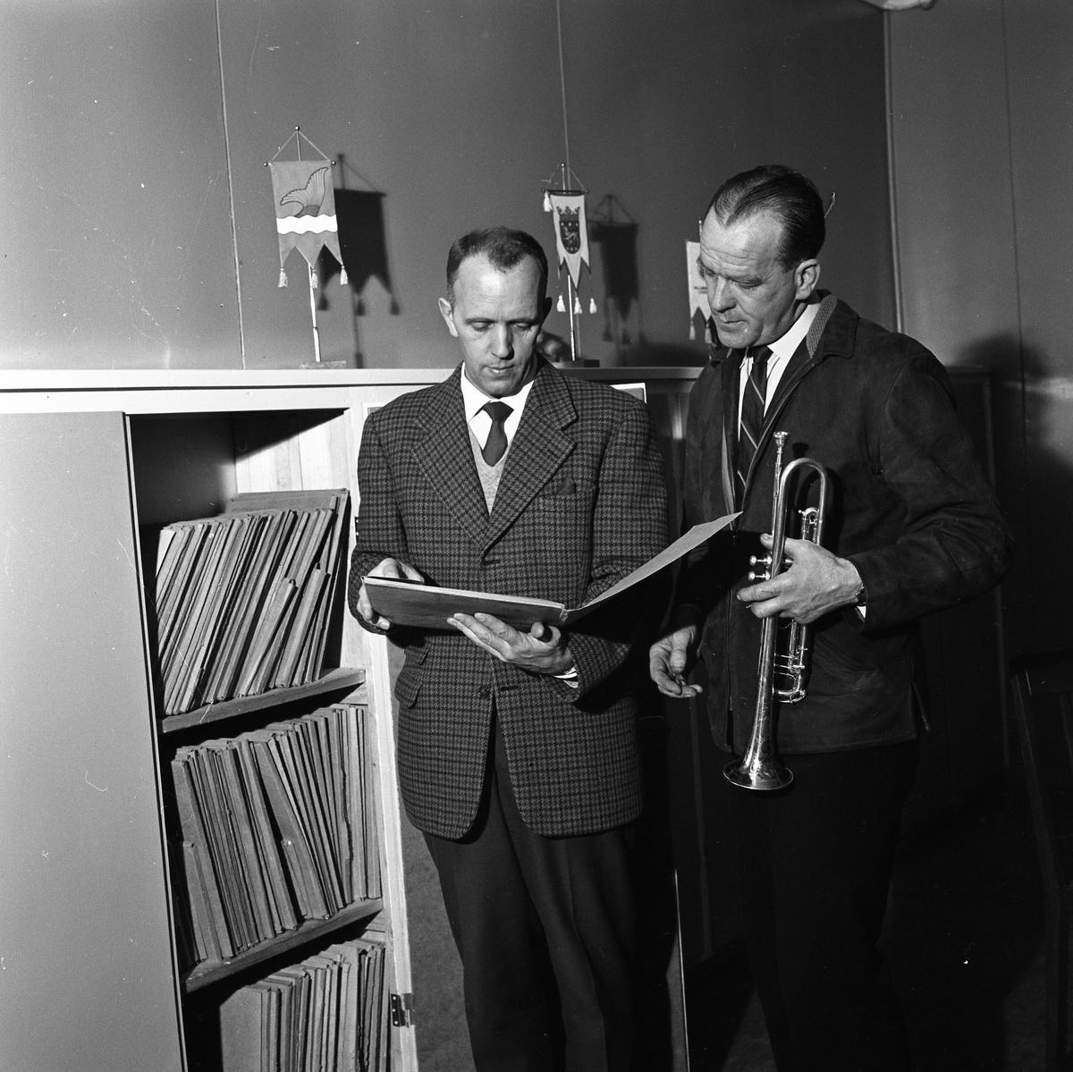 Arboga Blåsorkester repeterar En man plockar fram noter, mannen bredvid håller i en trumpet Vid sidan av dem står en hylla men noter.