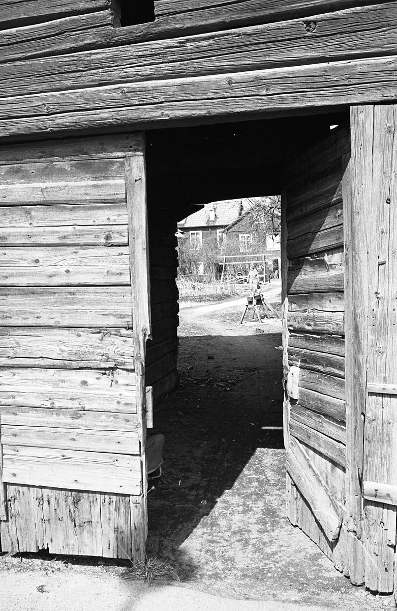 Uthus med liggande timmer. Porten står öppen. En kvinna i hatt och kappa ses på innegården. Äldre bebyggelse. Bostadsmiljö. Fotografens anteckning: Dokumentation av fastigheter i kvarteren söder och norr om ån. Bilder och beskrivning finns på Arboga Museum.
