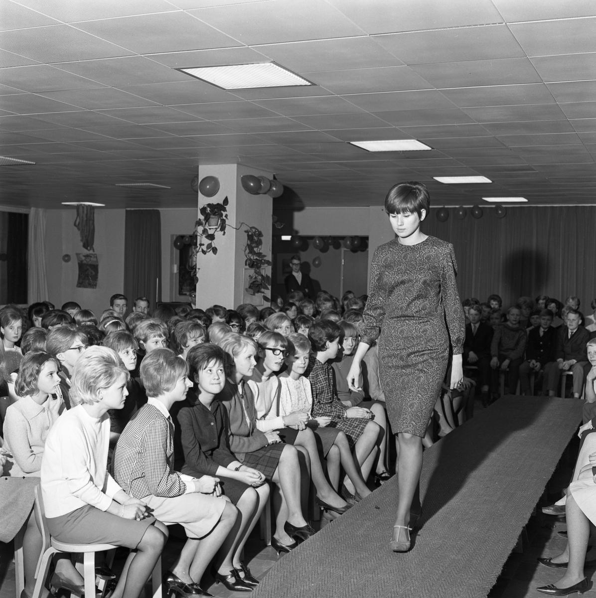 Elevernas modevisning i Stureskolan. Mannekängen visar en mönstrad klänning. Flickorna närmast catwalken är Inger Myrulf, Åsa Sundelin (rutig klänning) och Britt Antonsson Lokalen är dekorerad med ballonger
