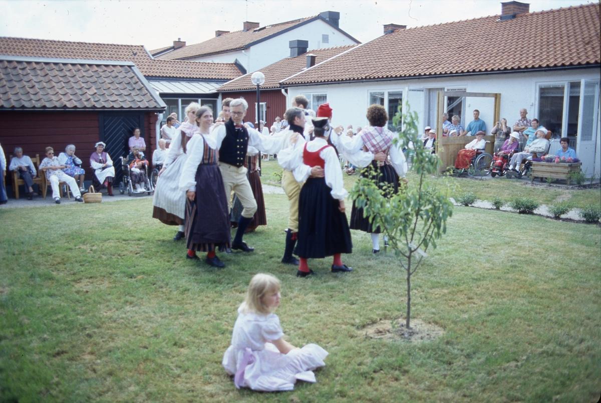Dansare från Arboga Folkdansgille uppträder på Strömsborgs äldreboende. Det är midsommartid. De äldre och deras anhöriga sitter efter väggarna, en del sitter i rullstol. Dansarna har uppvisning på gräsmattan på innegården. Alla bär folkdräkt. Kvinnan längst till vänster, som ser in i kameran, heter Birgitta Berglund. Hon dansar med Stefan Törnqvist. Framför dem dansar Ulla Olsson och Berndt Berglund. Paret längst till höger är Lars-Uno Olsson och Katarina Bäcklund. Birgitta och Katarina bär Västerfärnebodräkten (den kvinnliga folkdräkt som används mest i Västmanland).