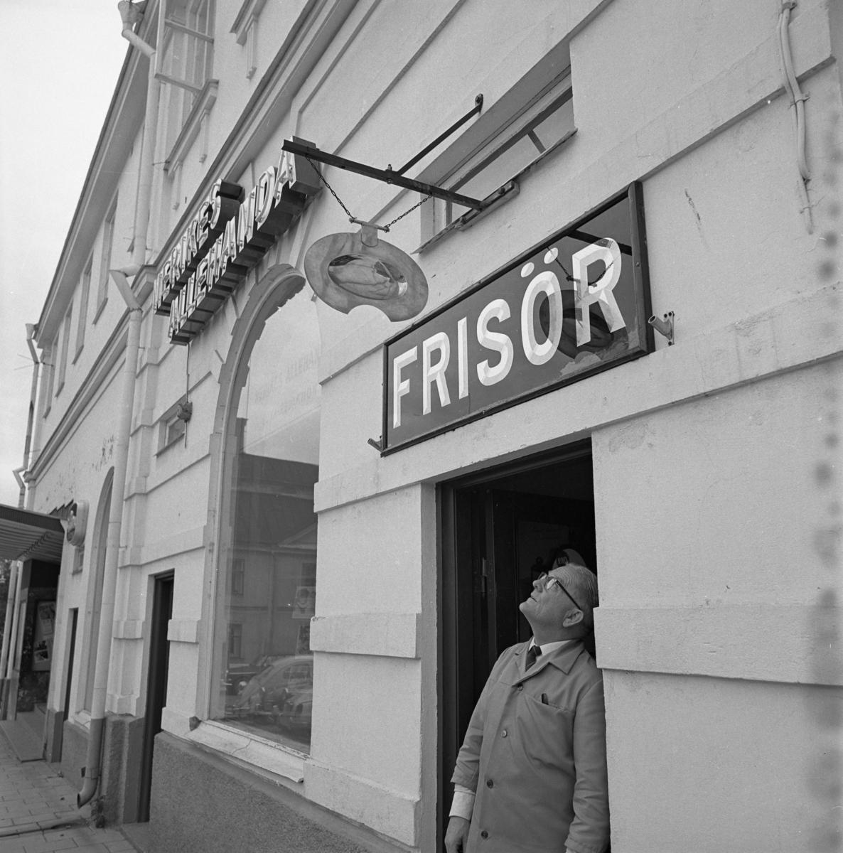 Frisörmästare Axel Fritiof Strandberg (kallad Atschy) vid sin salong på Stora torget, vägg i vägg med Nerikes Allehandas lokalkontor i Lundbergska huset.