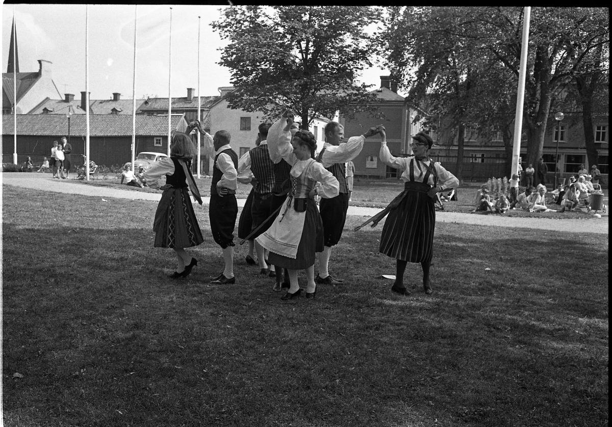 Dansuppvisning av gäster från vänorten Hallola. De bär folkdräkt. Publiken sitter i gräset. I bakgrunden ses fastigheter på Ahllöfsgatan och Nygatan. Baksidan av Stadskällaren ses till höger.