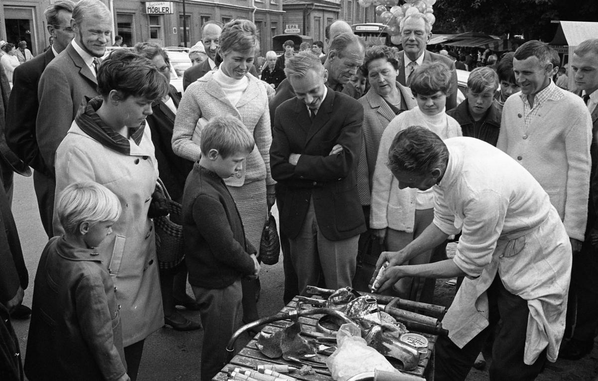 Höstmarknad på Järntorget. En försäljare demonstrerar sin produkt inför en intresserad publik. Mannen framför ballongerna är Verner Liljeborg. I bakgrunden ses möbelaffären och varuintaget till EPA