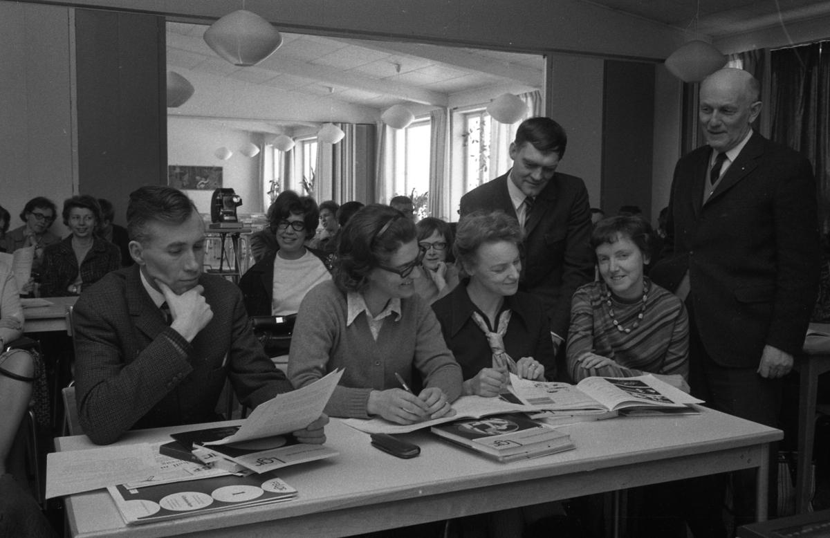 Lärare på kurs Främre bänkraden, från vänster: Bo Lannsjö, Barbro Erjö, Karin Eriksson och Berit Torshage. Stående, från vänster: Gunnar Bjurén och Bror Gustavsson (rektor). På andra bänkraden sitter Birgitta Göransson. På tredje bänkraden sitter Marianne Holmberg och längst bak, i salen, ses Inga-Britta Nanfeldt. Böcker och papper ligger på bänkarna och en filmprojektor står i det bakre rummet.