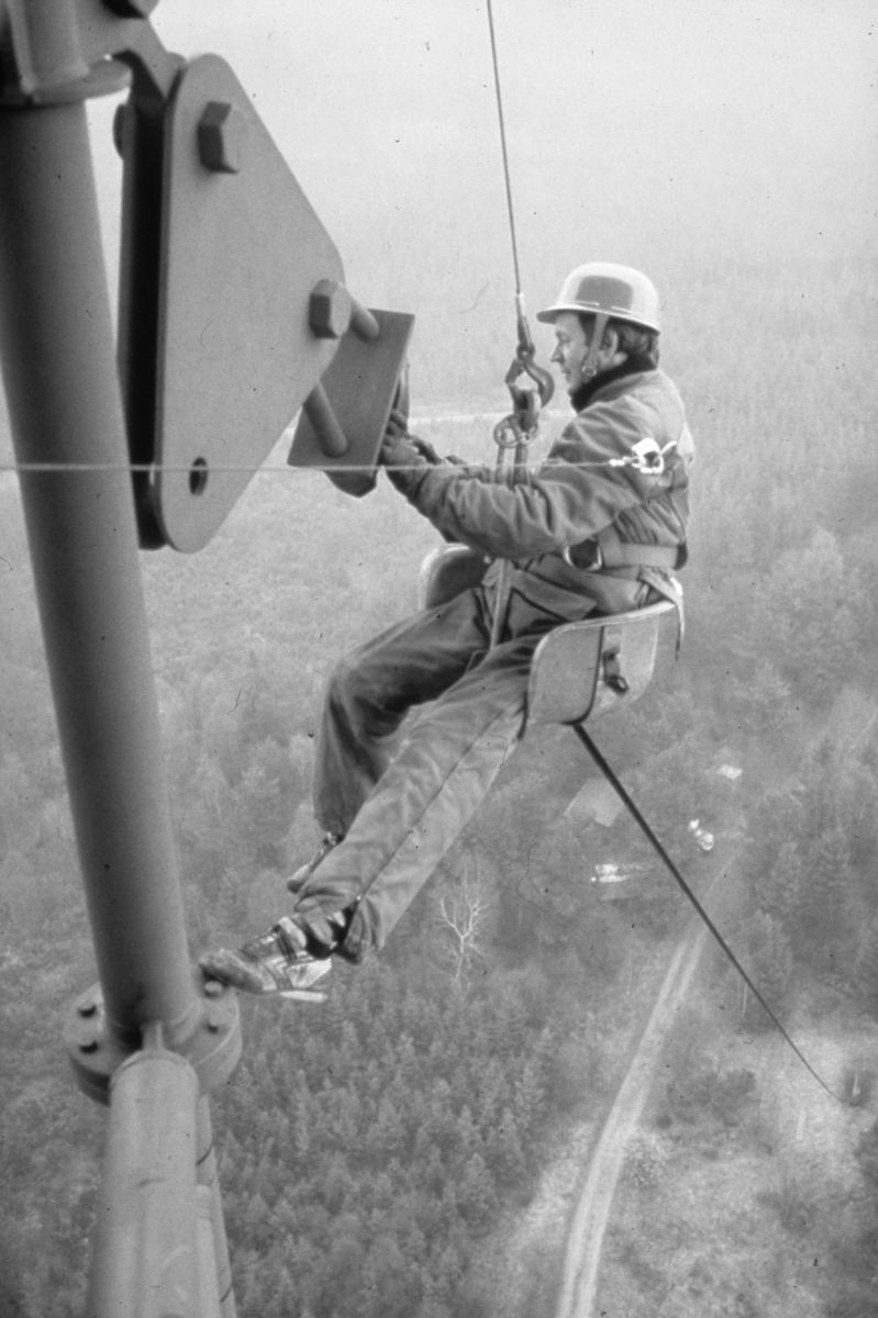 Ossian Möller på jobbet. Arbete på hög höjd. Man i mast. Han sitter på en sits som hänger i en wire. Han bär arbetskläder och skyddshjälm. Långt under honom ses skogen, en väg och några byggnader.