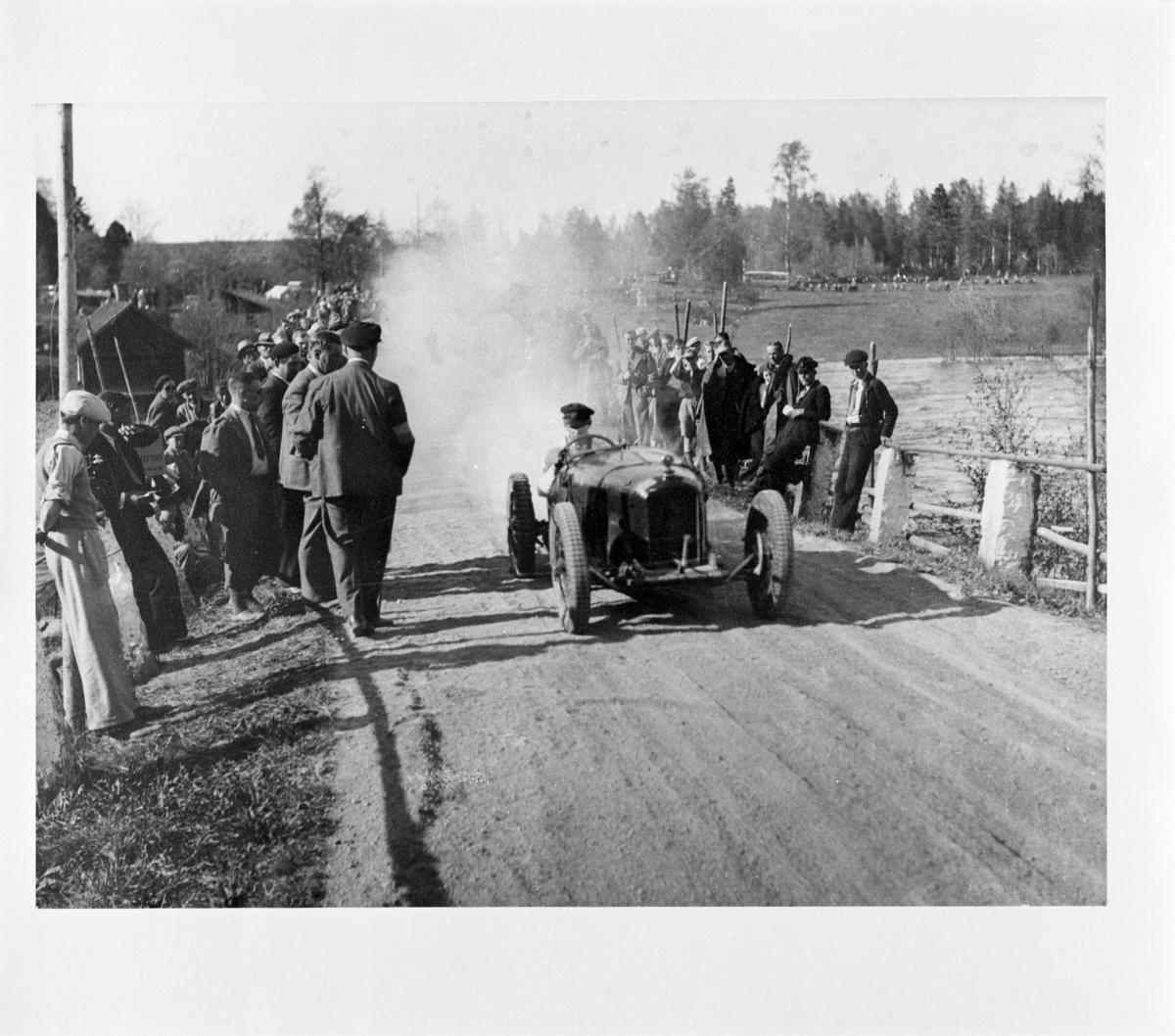 Reproduktion Röfors. En man kör en bil eller en traktor. Det kommer ett stort rökmoln bakom fordonet. Människor står i vägkanten och tittar på. Bilden är tagen på landet. Byggnader skymtar i bakgrunden.